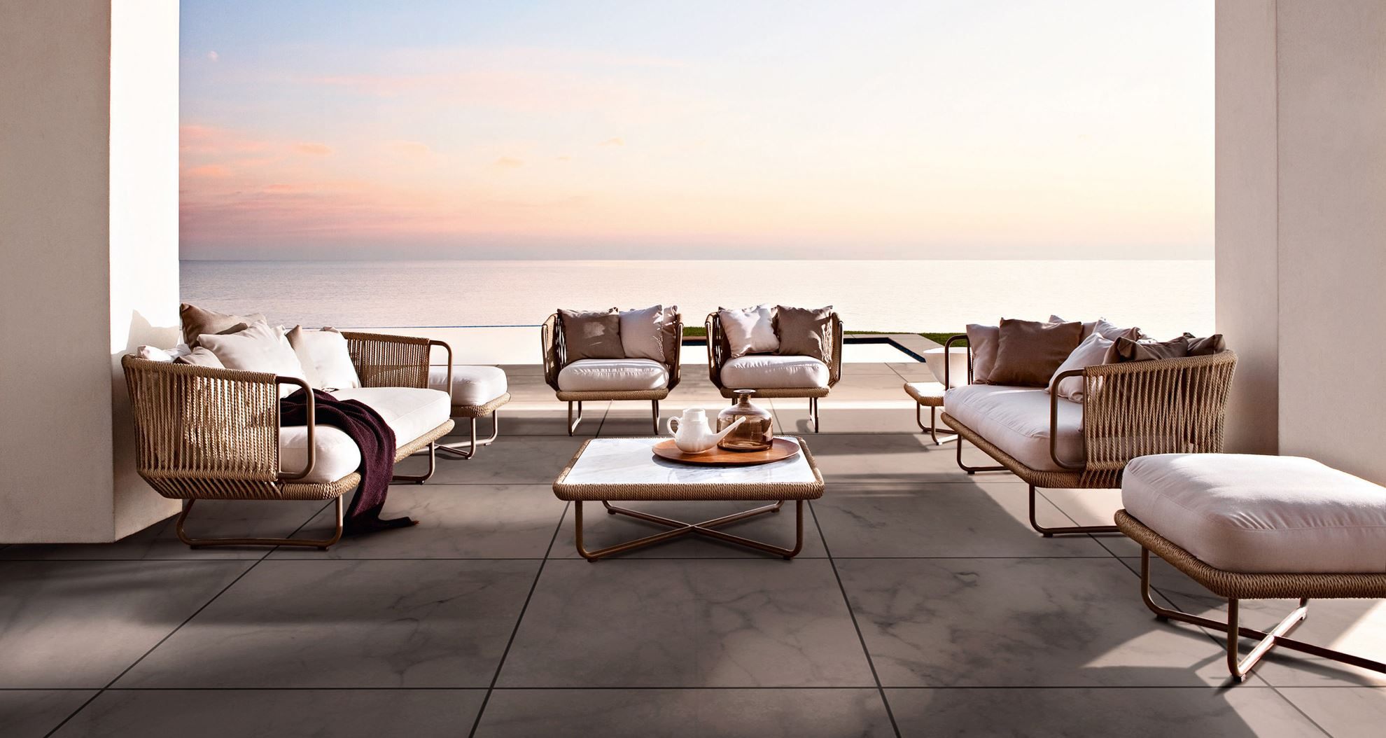 outdoor furniture on a hotel terrace in front of the sea