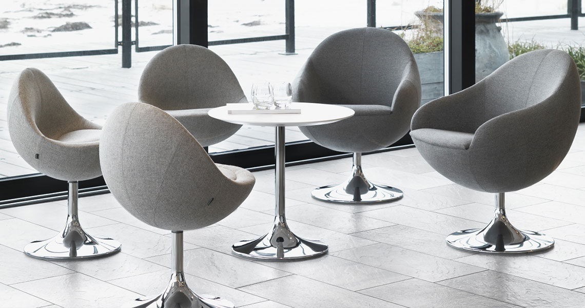 chrome pedestal chairs around a table with a chrome base