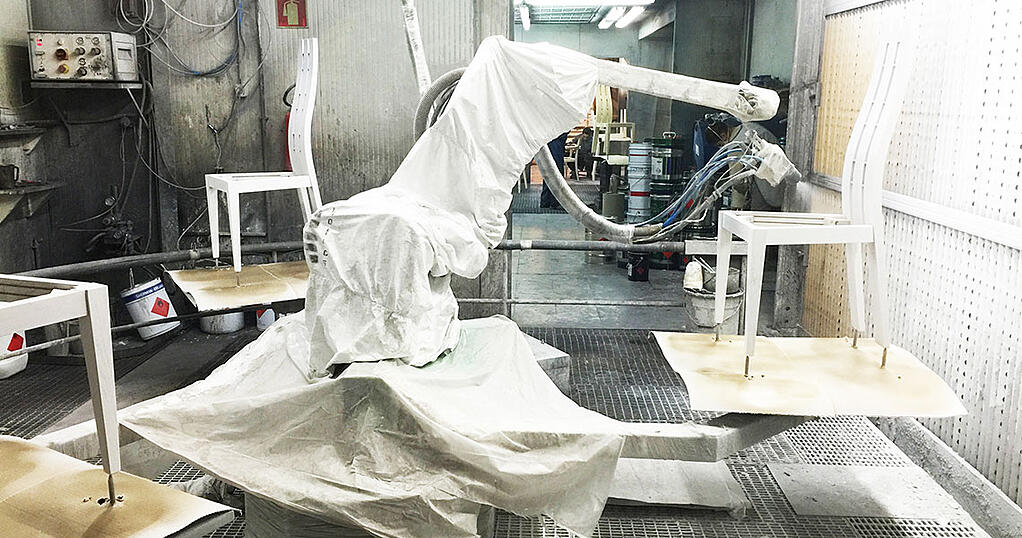 robot in a furniture factory painting a wooden chair white