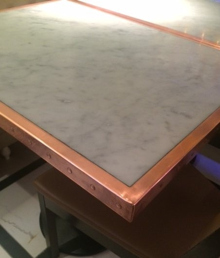 Marble table top with metal trim egde