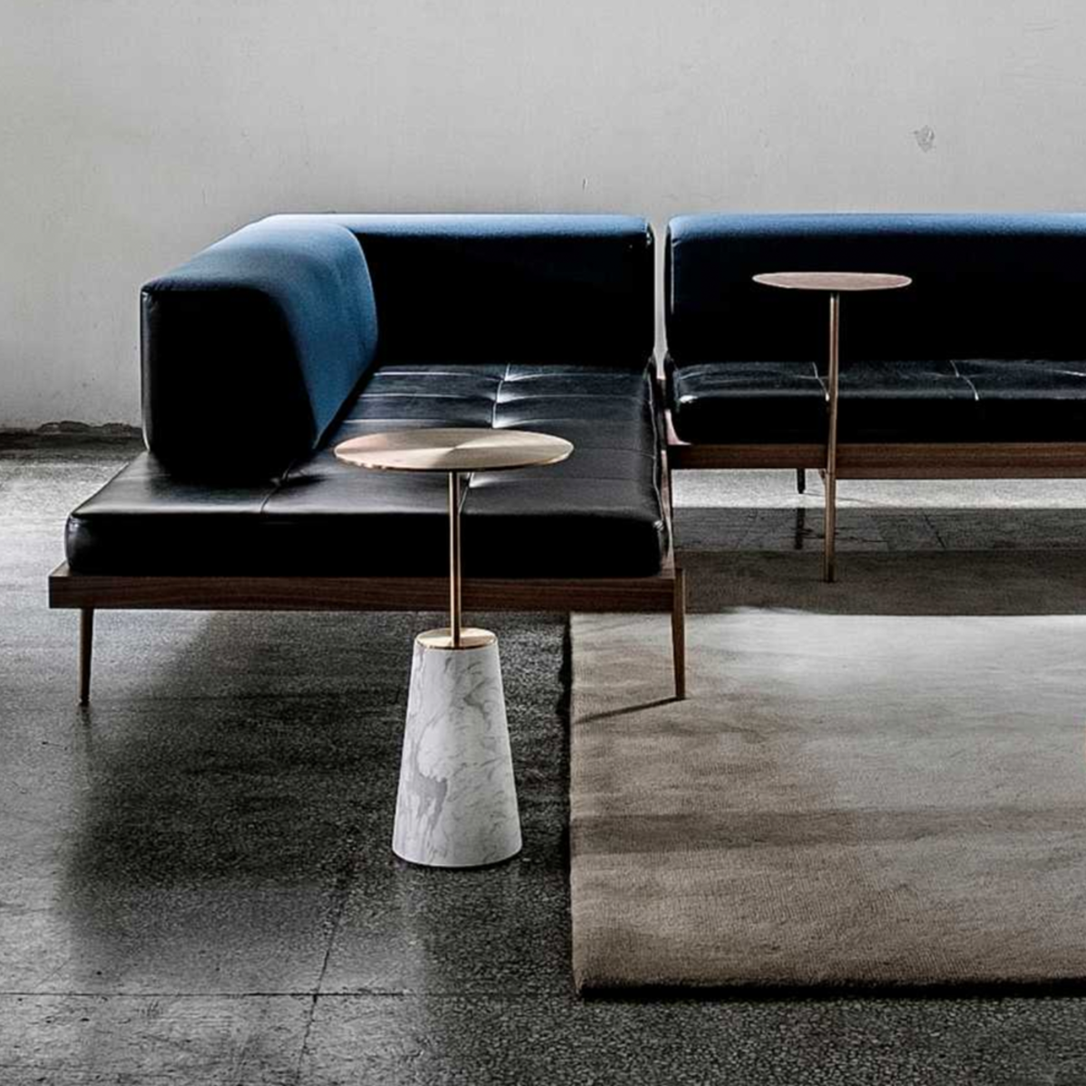 A photo of Bund side table with a sofa behind