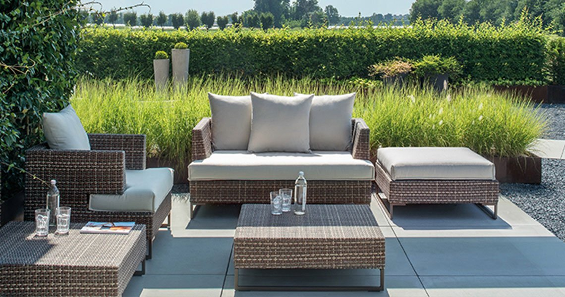 rattan furniture with cushions in grounds of hotel