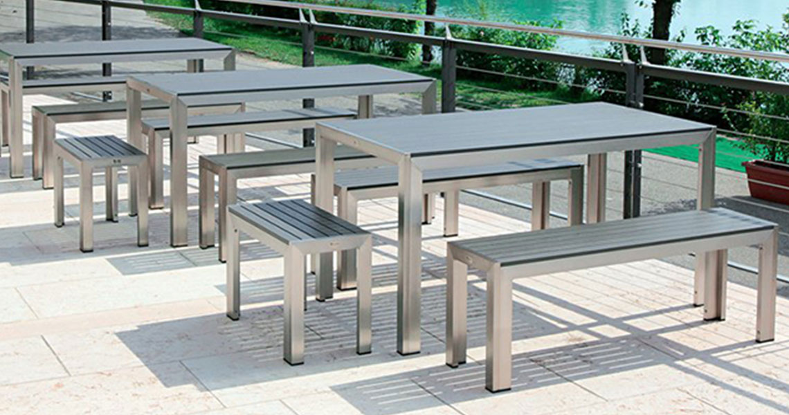 teak restaurant tables and benches by a lake